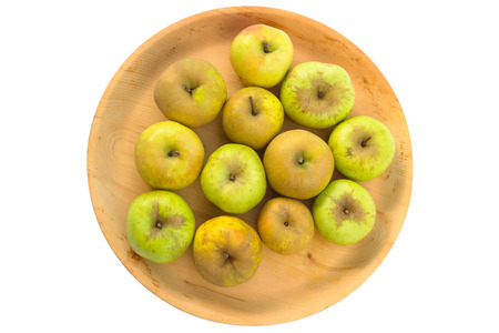 Wooden bowl full of imperfect looking organic apples with unconventionally raised method, no genetically modified organism techniques Stock Photo