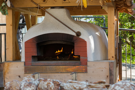 woodfire: Old traditional stone bread oven stove with burning wood fire and red flames inside Stock Photo