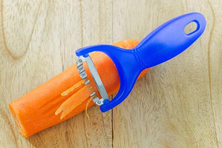 slicer: Stainless steel knife slicer tool in blue shredding carrot on a wooden background Stock Photo