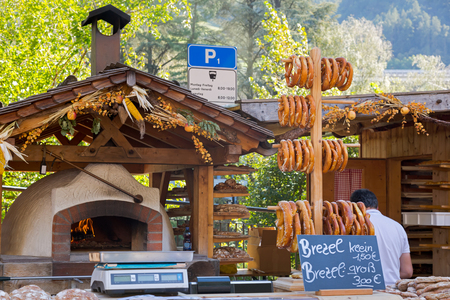 woodfire: Small and big size of Pretzels selling in front of old traditional stone bread oven stove with burning wood fire and red flames inside