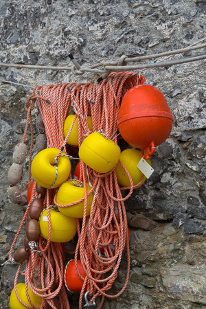 Ropes with floats to tie boats and used in fishing industry hanging on the wall in Italy, southern Europe