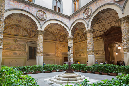 FLORENCE, ITALY - SEPTEMBER 2016 : People walk inside Old Palace, Palazzo Vecchios first Courtyard, town hall of Florence, Italy with Putto cupid fountain in the middle on September 21, 2016. Frescoes on walls are cities of Austrian Habsburg monarchy
