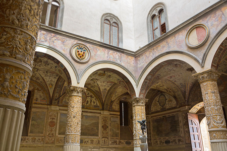 FLORENCE, ITALY - SEPTEMBER 2016 : Interior details of Old Palace, Palazzo Vecchios first Courtyard, town hall of Florence, Italy with Putto cupid fountain in the middle on September 21, 2016. Frescoes on walls are cities of Austrian Habsburg monarchy