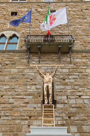 exhibiting: FLORENCE, ITALY - SEPTEMBER 2016 : Shiny bronze sculpture statue of The Man Who Measures the Clouds, man standing atop a ladder with ruler exhibiting at Piazza della Signoria in Florence, Italy on September 21, 2016. Made by Jan Fabre, Belgian artist Editorial