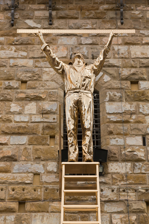 measures: FLORENCE, ITALY - SEPTEMBER 2016 : Shiny bronze sculpture statue of The Man Who Measures the Clouds, man standing atop a ladder with ruler exhibiting at Piazza della Signoria in Florence, Italy on September 21, 2016. Made by Jan Fabre, Belgian artist Editorial