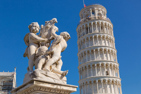 PISA, ITALY - SEPTEMBER 2016 : Leaning Tower of Pisa and status of cherubs winged angels in Pisa, Italy on September 22, 2016. Pisa Tower (Torre pendente di Pisa) is a freestanding bell tower campanile of cathedral