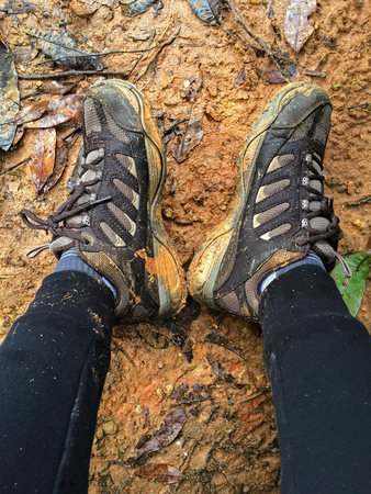 muddy clothes: Woman with dirty brown hiking shoes resting on wet muddy area full of dried leaves Stock Photo