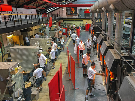 glassblower: KUFSTEIN, AUSTRIA - SEPTEMBER, 2016 : Male workers working on making glass at Riedel in Kufstein, Austria on September 19, 2016. Riedel is the wine glass blowing manufacturer company Editorial