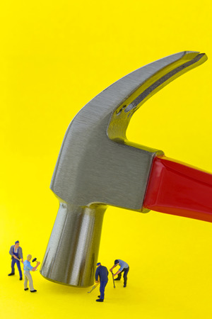 Steel claw hammer with red handle on yellow background with small mini miniature worker men working nearby