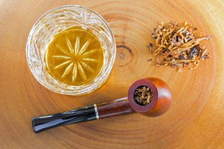 Glass of single malt scotch whisky next to classic blended aromatic pipe tobacco on bright wooden background   Stock Photo