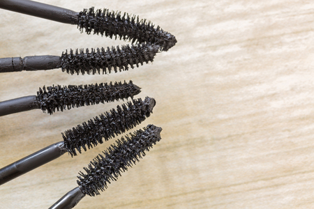 Closeup of various mascara brushes, cosmetic to enhance eyelashes from different brand on wooden floor with copyspace  Stock Photo