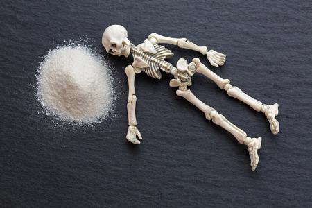 De witte beenderen die van het skelet lijkend naast gevaarlijk wit fijn poeder zoals cocaïne op zwarte steenachtergrond rusten