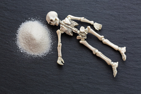 White skeleton dead body bones resting next to dangerous white fine powder like cocaine on black stone background