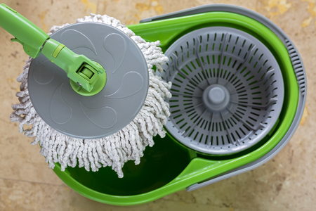 absorption: Used round spin mop with microfiber head, green handle on cleaning bucket with blurred yellow tiles floor