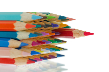 Soft focus close up tip of colorful colored pencils with sharp red one standing out, on white background