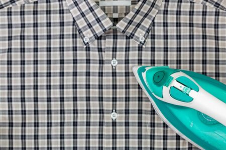steam output: Steam iron in green with aluminum soleplate, water in tank, ironing blurred checked clothes black white shirt