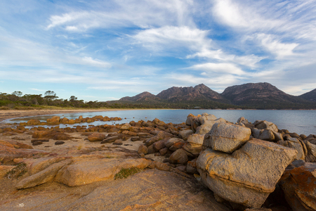 Rocky coastline on Freycinet national park beach in the evening. Big granite rocks during sunset with view of Hazards mountain range from Coles Bay. East coast of Tasmania, Australia Stock Photo