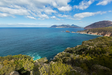 Turquoise waters of Carp bay, view from Cape Tourville Lighthouse lookout - Seascape photo, cliff coastline, green mountain, blue sky at Freycinet National Park, Tasmania, Australia Stock Photo