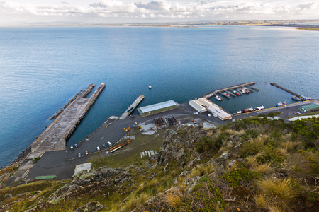 High angle view of Fishermans Wharf at Stanley Harbor and Bass sea Strait from lookout on top of the Nut Plateau tableland in Tasmania, Australia. The nut is old volcanic plug of basalt with the height of 143 meters rising from ocean. Stock Photo