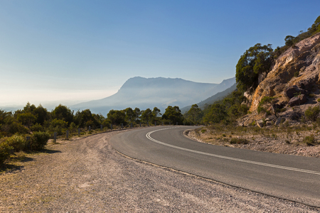 australasia: Curvy Olivers road at the curve with misty view of southern side of Mt Roland in background. Taken from  Round Mt Claude Lookout in Tasmania, Australia Stock Photo