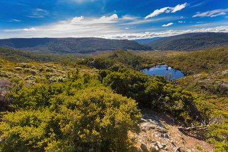 Opinión de alto ángulo de la piscina de Wombat rodeada por las montañas verdes en la montaña de Cradle, parque nacional del lago St Clair. Otoño en Tasmania, Australia