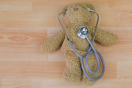 Teddy bear on wooden floor with stethoscope, acoustic medical device with earpieces in ears   Stock Photo