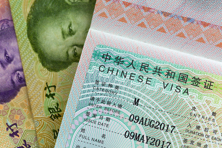Closeup of approved China Business Visa (M Visa) on Chinese Yuan currency banknotes money Imagens