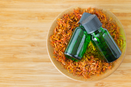Pure Safflower essential concentrate oil extract in green bottle on bowl of dried safflower plant on wooden background with copyspace (Carthamus tinctorius)