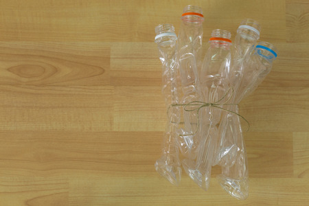 emptied: Group of emptied recyclable clear plastic mineral soda water bottles tied together on wooden background with copyspace