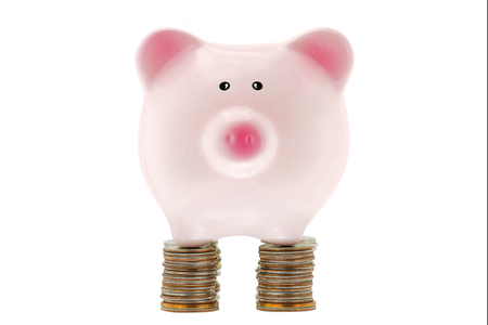 budgets: Pink ceramic piggybank standing on stack of many coins of the United States dollar, strong foundation of money saving, isolated on white