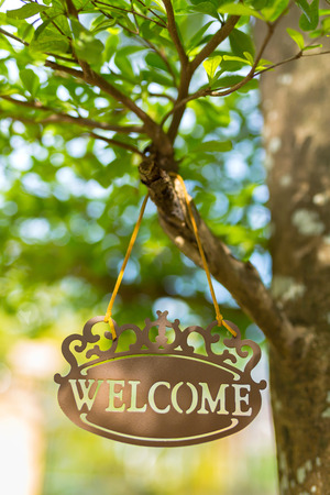 Metal welcome sign hang on tree with bokeh blurred background in the garden.