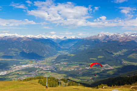 Paragliders take off near ski lift with Austrian Alps mountain range, valley, snowy glacier mountains in background, Autumn view from Mount Kronplatz, South Tyrol, Italy, Europe  Stock Photo