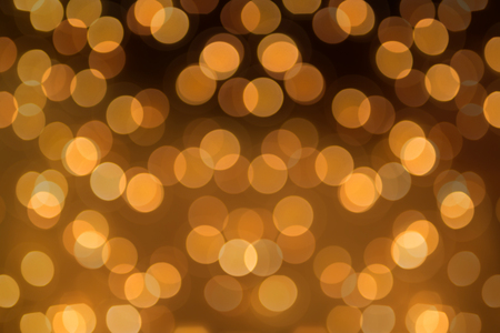 Big round Bokeh in golden yellow on dark brown background. Abstract Blurred circles background photo