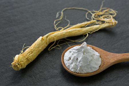 Radix Ginseng root next to White rice and Chinese Ginseng clarifying polishing facial mask in wooden spoon on black stone background