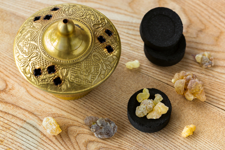 Aromatic yellow resin gum from Sudanese Frankincense tree on Arabian charcoals to burn aromatic incense in brass burner.  写真素材