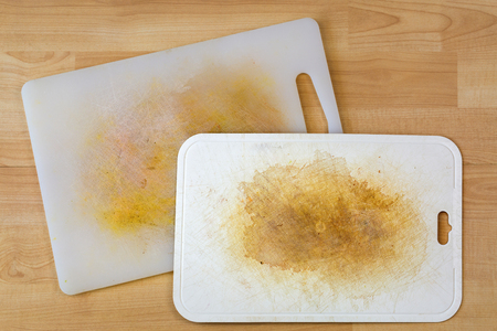 Dirty white plastic cutting board with dark stains, scratch, on wooden background