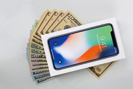 BANGKOK, THAILAND - JANUARY 2018 : Box of new iPhone X (iPhone 10) on American banknote money on marble background on January 17, 2018 in Bangkok, Thailand Редакционное
