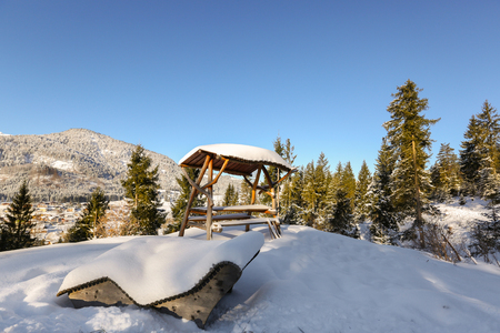 Wooden sunbath lounge bench chair, outdoor picnic table with roof under snow on sunny day with blue sky, winter in Tyrol, Europe