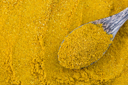 Top view of yellow spicy Curry Powder in wooden spoon, main ingredient seasoning to cook Asian curry on blurred spice background Stock Photo