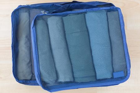 Sacs en maille cubique avec vêtements roulés, t-shirt, pantalon. Ensemble d'organisateur de voyage pour aider à emballer les bagages facilement, bien organisé