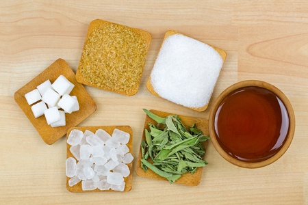 Sugar cubes, brown sugar crystals, granulated white sugar, rock sugar, stevia, honey, Different types of sweetness, top view on wooden background