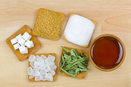 Zollette di zucchero, cristalli di zucchero di canna, zucchero bianco granulato, zucchero di roccia, stevia, miele, diversi tipi di dolcezza, vista dall'alto su fondo di legno