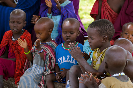TANZANIA, EAST AFRICA - APRIL 2018 : Maasai African kids singing a song under Acacia tree as outdoor school on April 13, 2018 in Tanzania, East Africa.