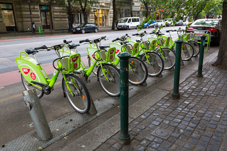 BUDAPEST, HUNGARY - JULY 2018 : Green bicycles from MOL BuBi docking by street in Budapest, Hungary on July 18, 2018. Bubi is a bicycle sharing network in Hungary.