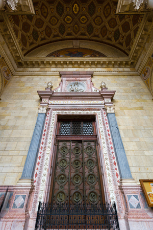BUDAPEST, HUNGARY - JULY 2018 : Medallions on wooden door showing busts of the 12 apostles at St. Stephens Basilica in Budapest, Hungary on July 18, 2018. Редакционное