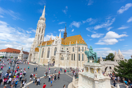 BUDAPEST, HUNGARY - JULY 2018 : People walking near equestrian statue of St Stephen, first king of Hungary, in front of Matthias Church, Castle Hill, Budapest, Hungary on July 19, 2018