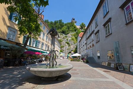 GRAZ, AUSTRIA - JULY 2018 : Fountain on Schlossbergplatz with background of staircase going up to Schlossberg Castle Hill in Graz, Austria on July 20, 2018.