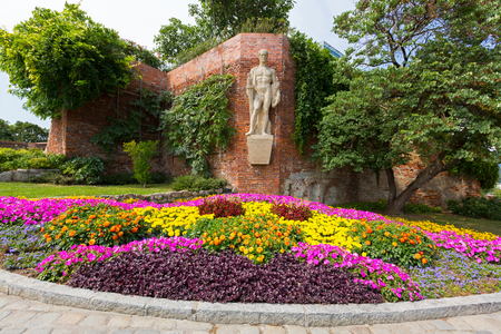 GRAZ, AUSTRIA - JULY 2018 : Sculpture titled Furchtlos und treu INF.RGT.27 - 1682-1918, meaning Fearless and faithful, on fortress wall above colorful flower bed at Schlossberg Castle Hill in Graz, Austria on July 20, 2018.