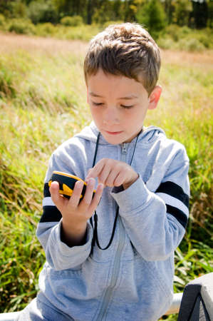 young boy looking at gps while geocaching photo