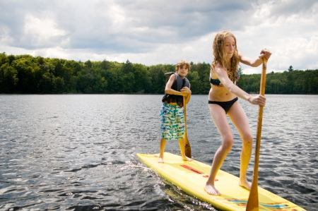 girl and boy on a stand up paddle board photo